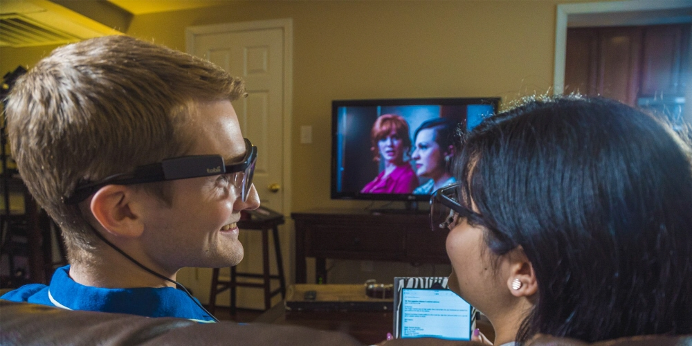 Two people in the living room wearing Tobii Pro Glasses 2 and watching the Mad Man TV show.