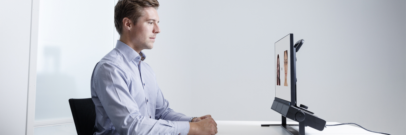 A young man seats in front of the Tobii Pro Spectrum eye tracker