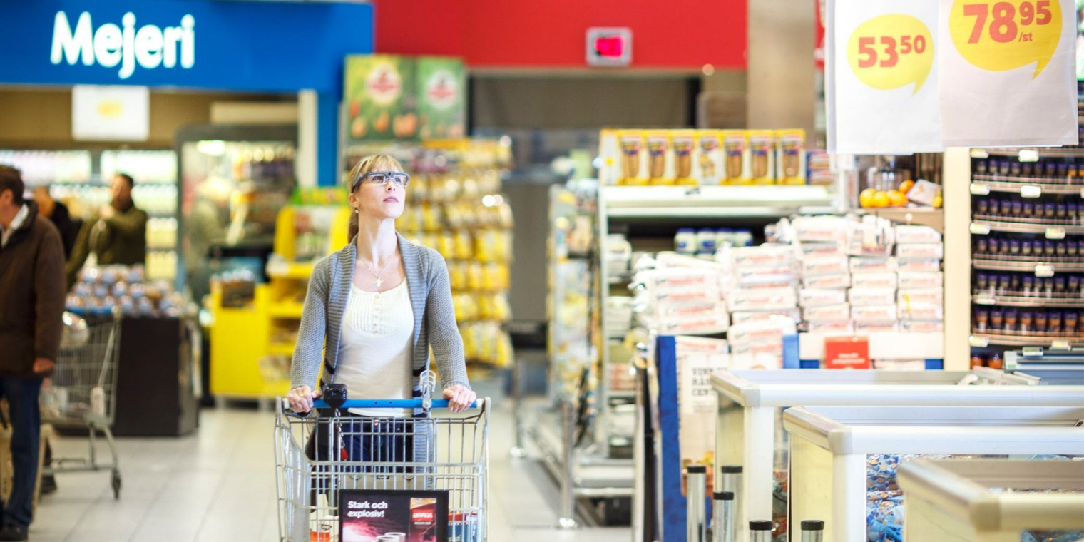 A woman wearing Tobii Pro Glasses 2 moves along the aisle.