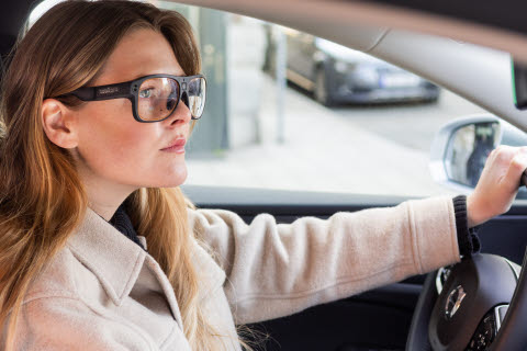 Woman using Tobii Pro Glasses 3 wearable eye trackers while driving