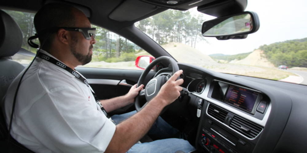 A man driving an Audi car wearing Tobii Pro Glasses eye tracker.