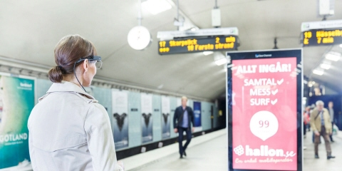 A woman wearing Tobii Pro Glasses 2 looks at an advertisements.