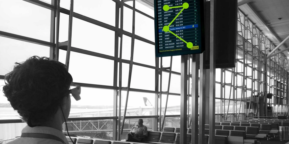 A test participant wearing Tobii Pro Glasses 1 looks at the electronic timetable display in the airport.