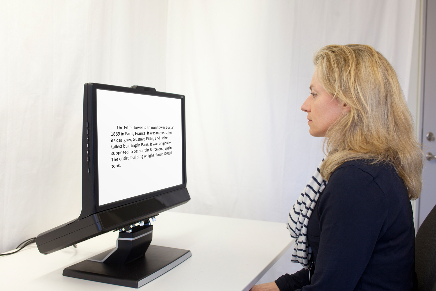 A woman reading a text displayed on the screen of the Tobii Pro TX300