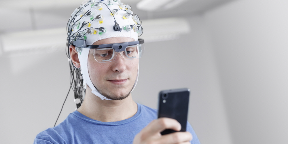 A person wearing Tobii Pro Glasses 2 synchronized with EEG