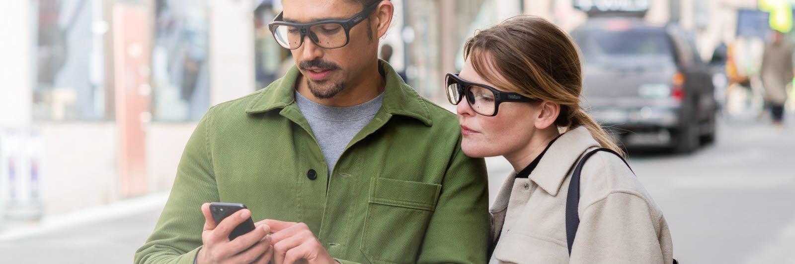 A couple wearing Tobii Pro Glasses 3 looking at a mobile