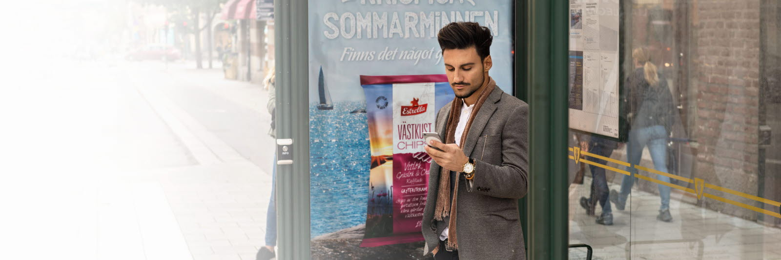 Man looking at mobile phone advertising at a bus stop